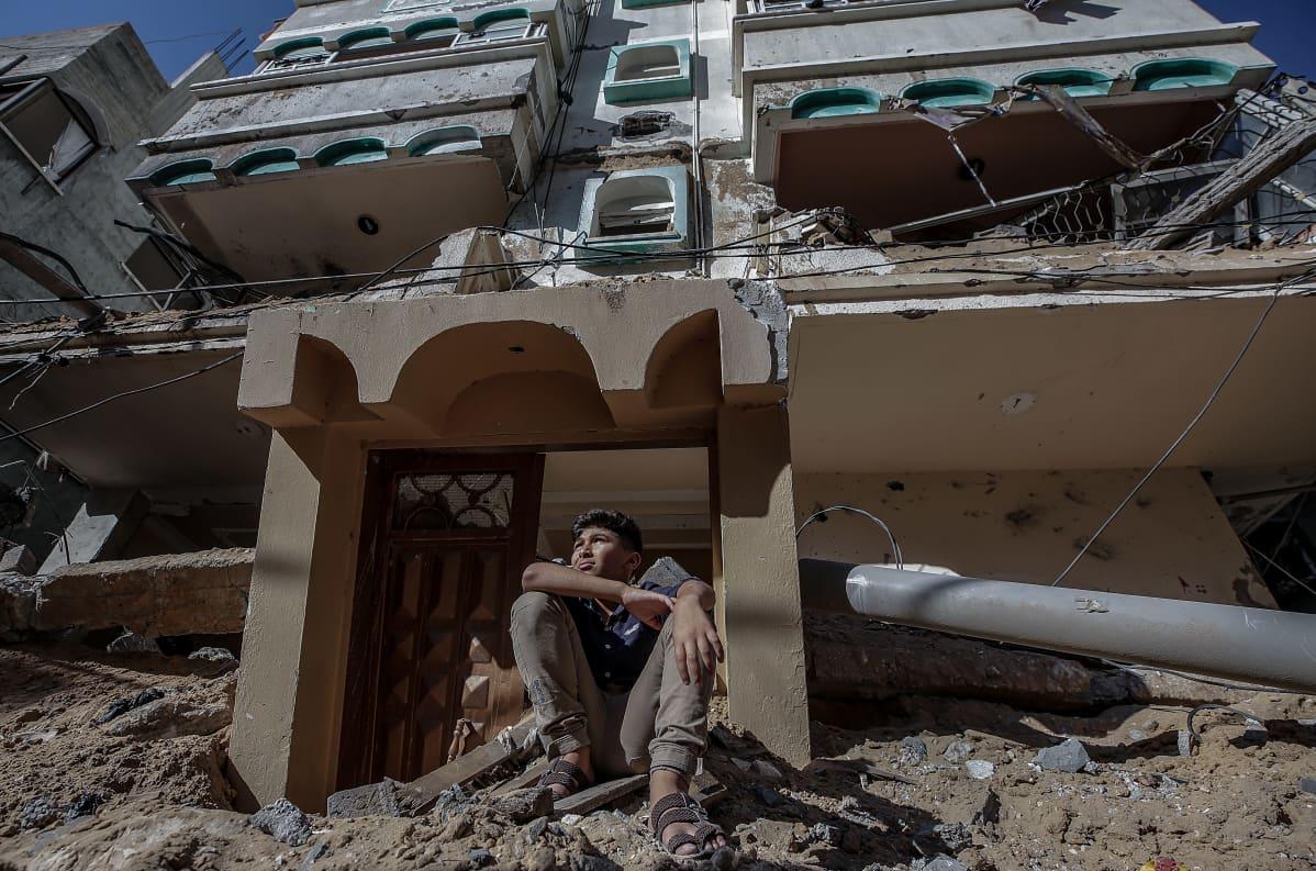 Palestiinalaispoika istuu Israelin pommittaman talon raunioilla Gazassa 13.5.2021.