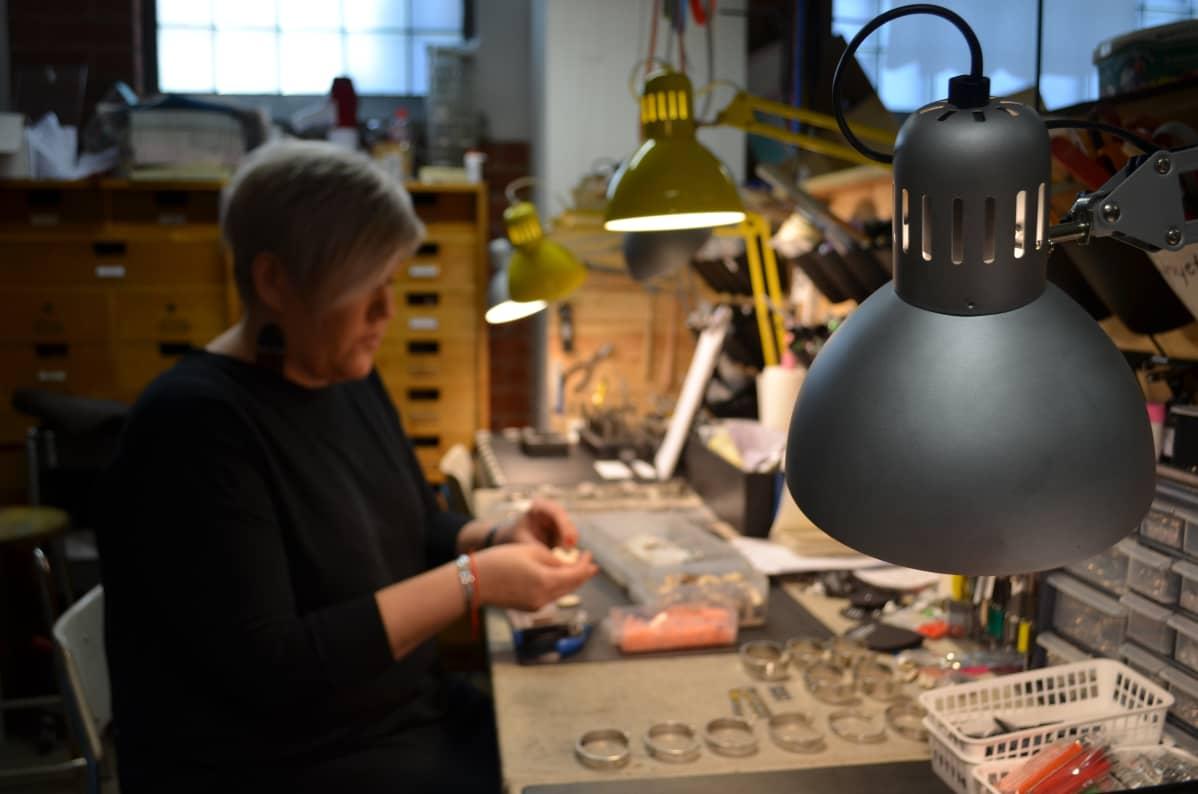 Nainen työpöydän ääressä kokoamassa korvakoruja.