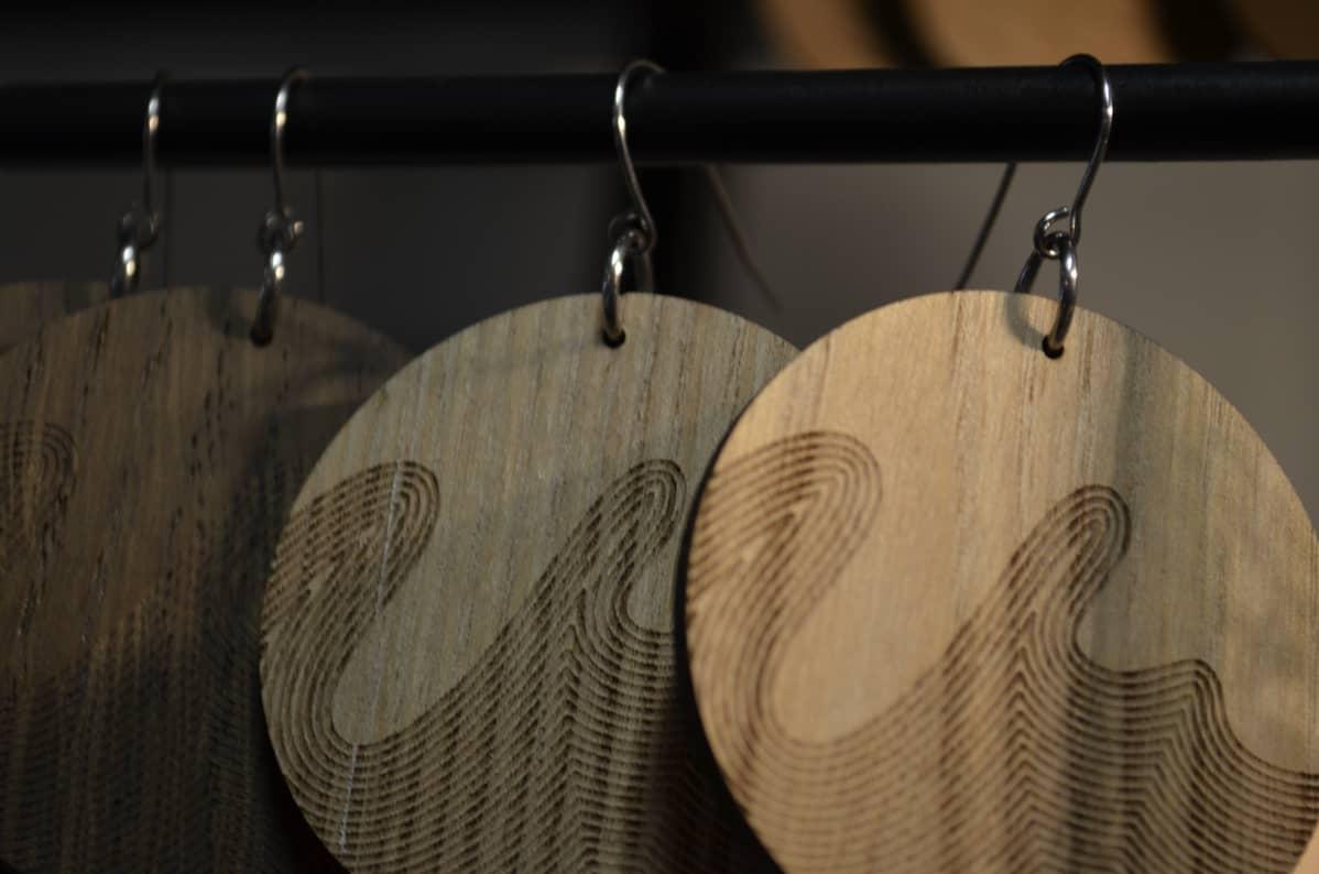 Puuvanerista leikattuja pyöreitä korvakoruja roikkumassa telineessä.