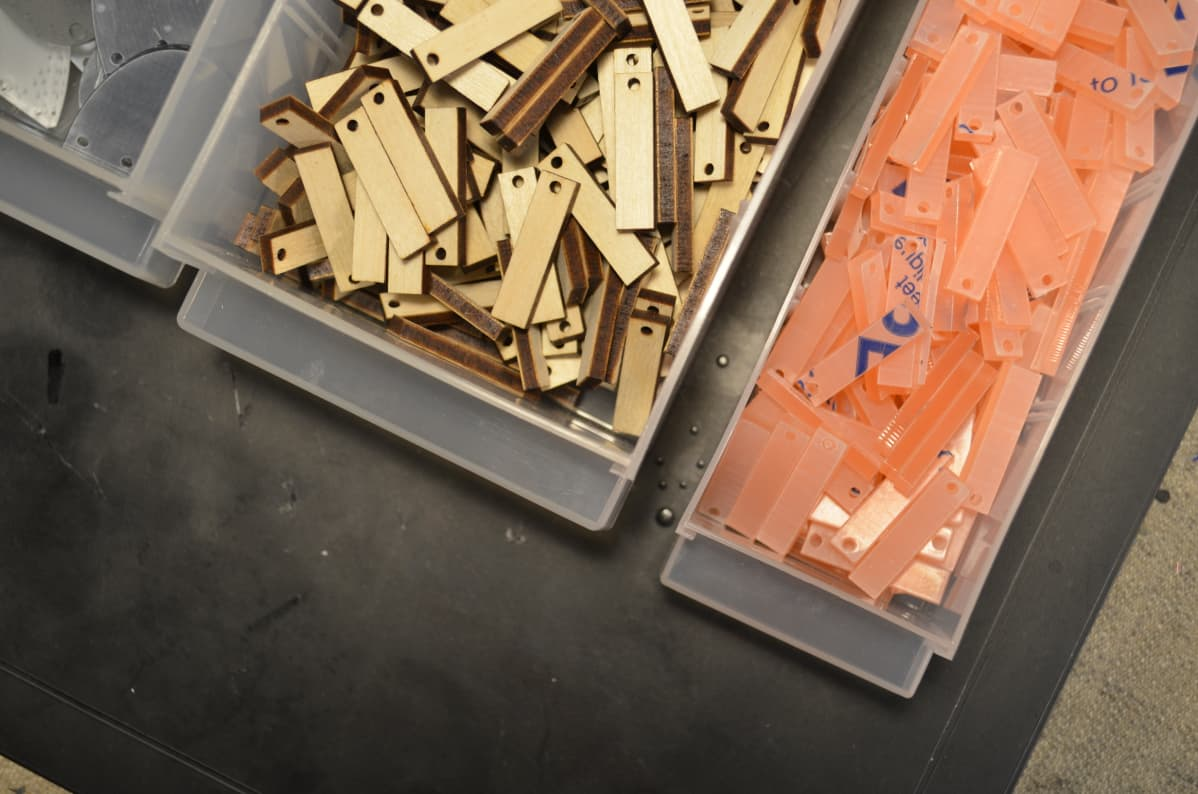 Laserleikkurilla leikattuja korujen  puisia ja akryylisiä osia rasioissa.