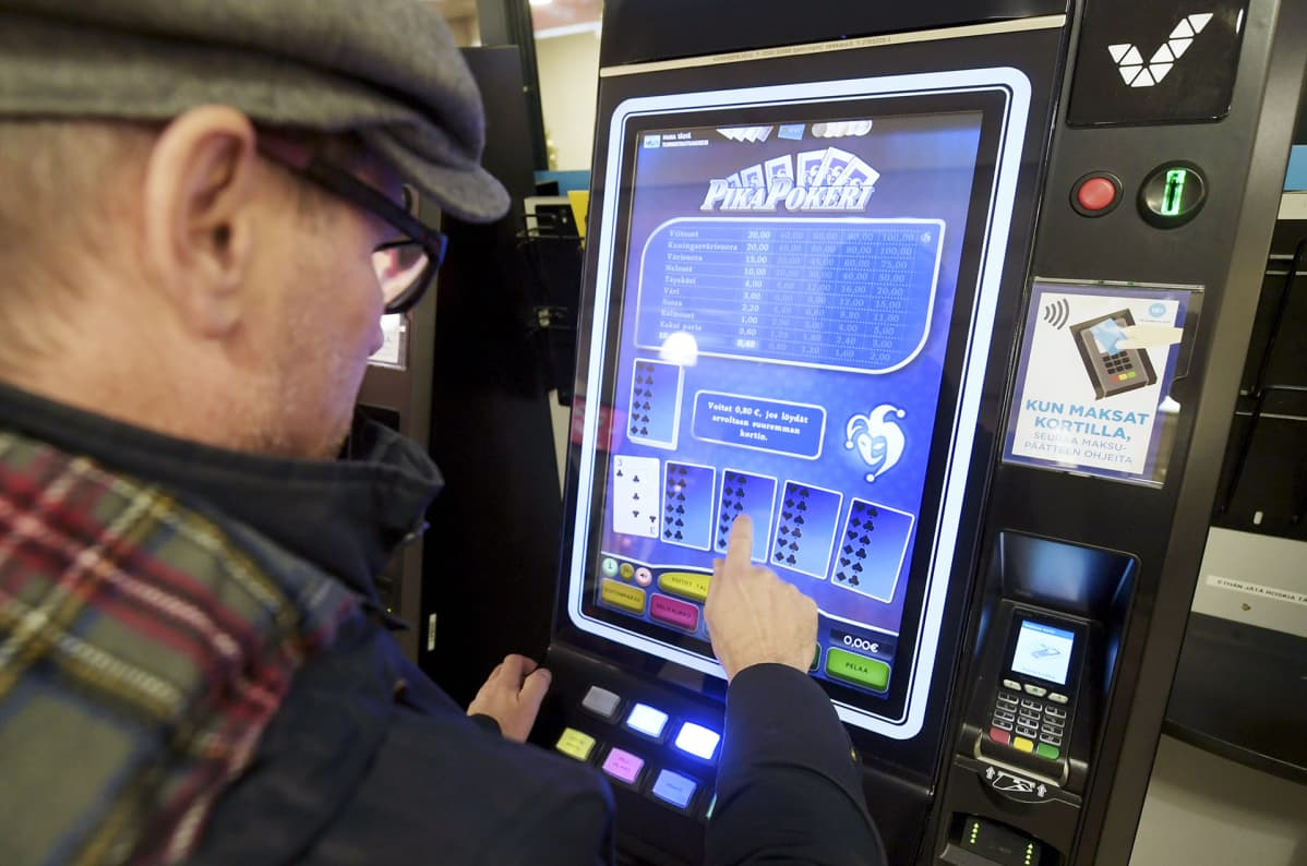 Mies pelaa peliautomaattia marketissa