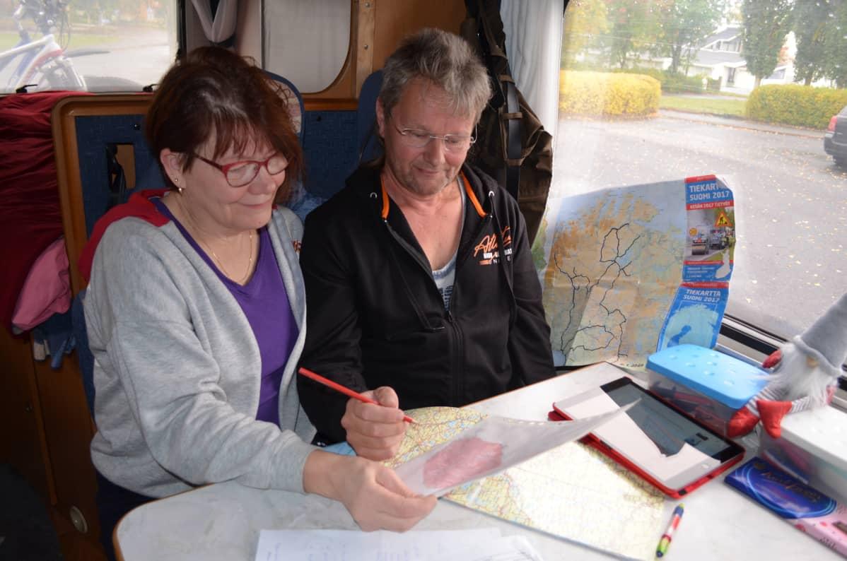 Kuntakiertäjät Mirja Kononen ja Aimo Mattila asuntoautossaan karttojen äärellä.