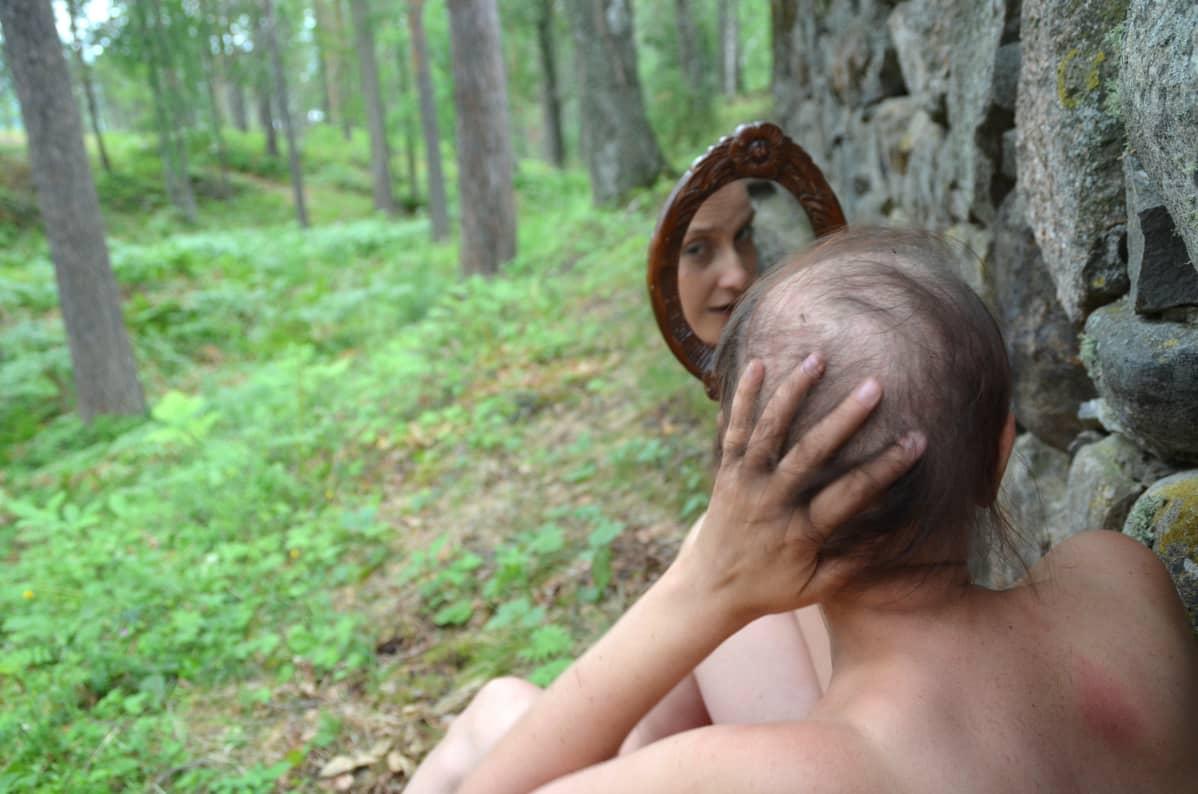 nainen katsoo itseään peilistä