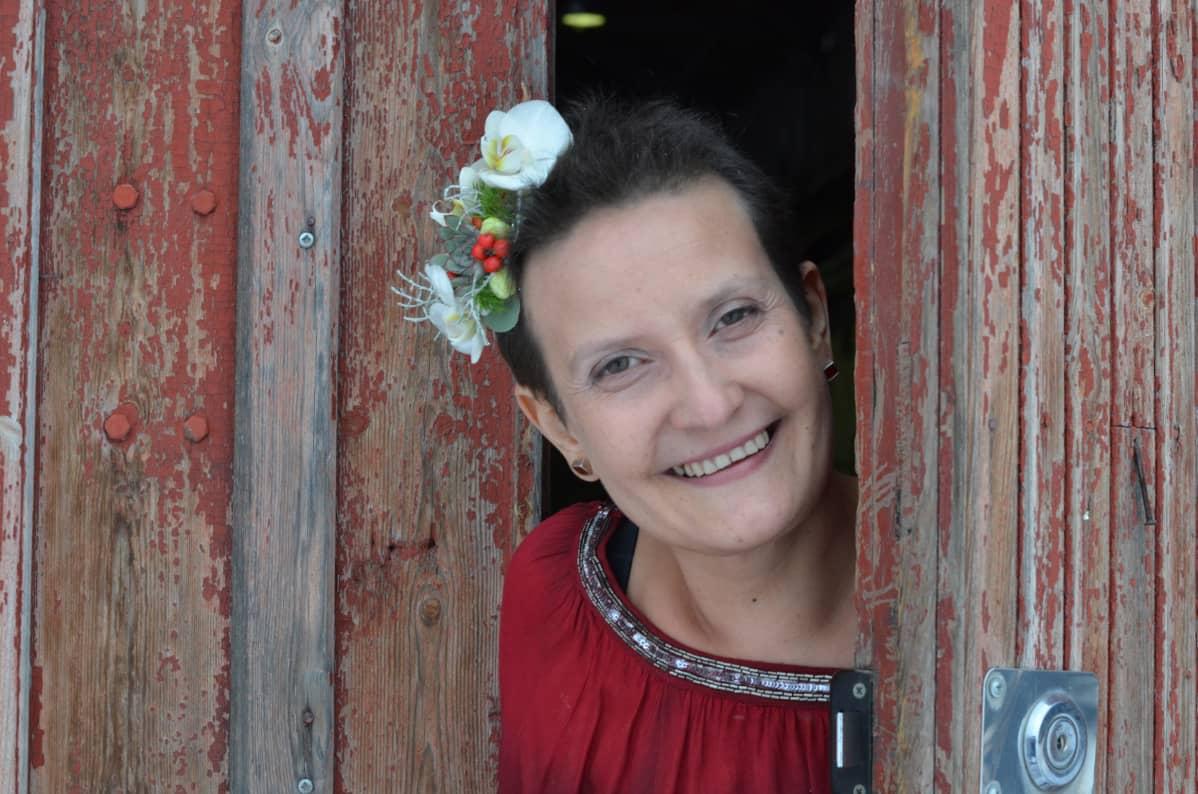 nainen hymyilee kukkia hiuksissaan