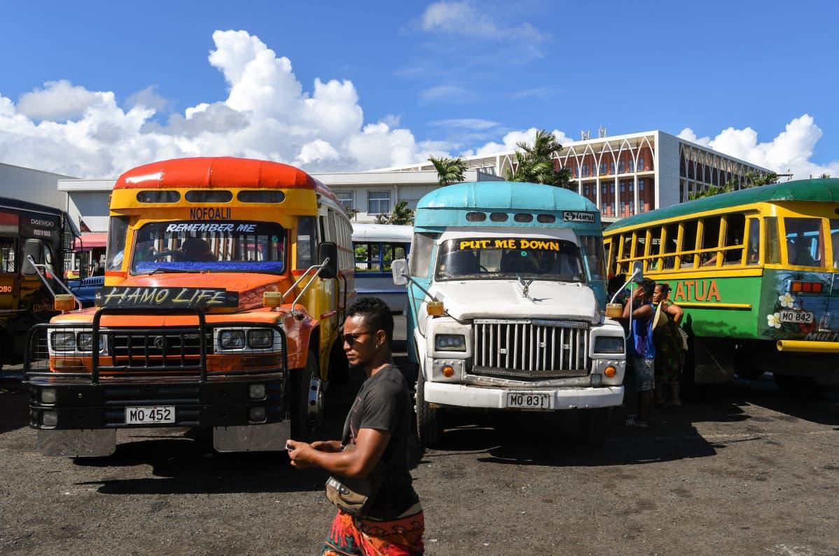 Mies kävelee bussien ohi Samoan pääkaupungissa Apiassa.