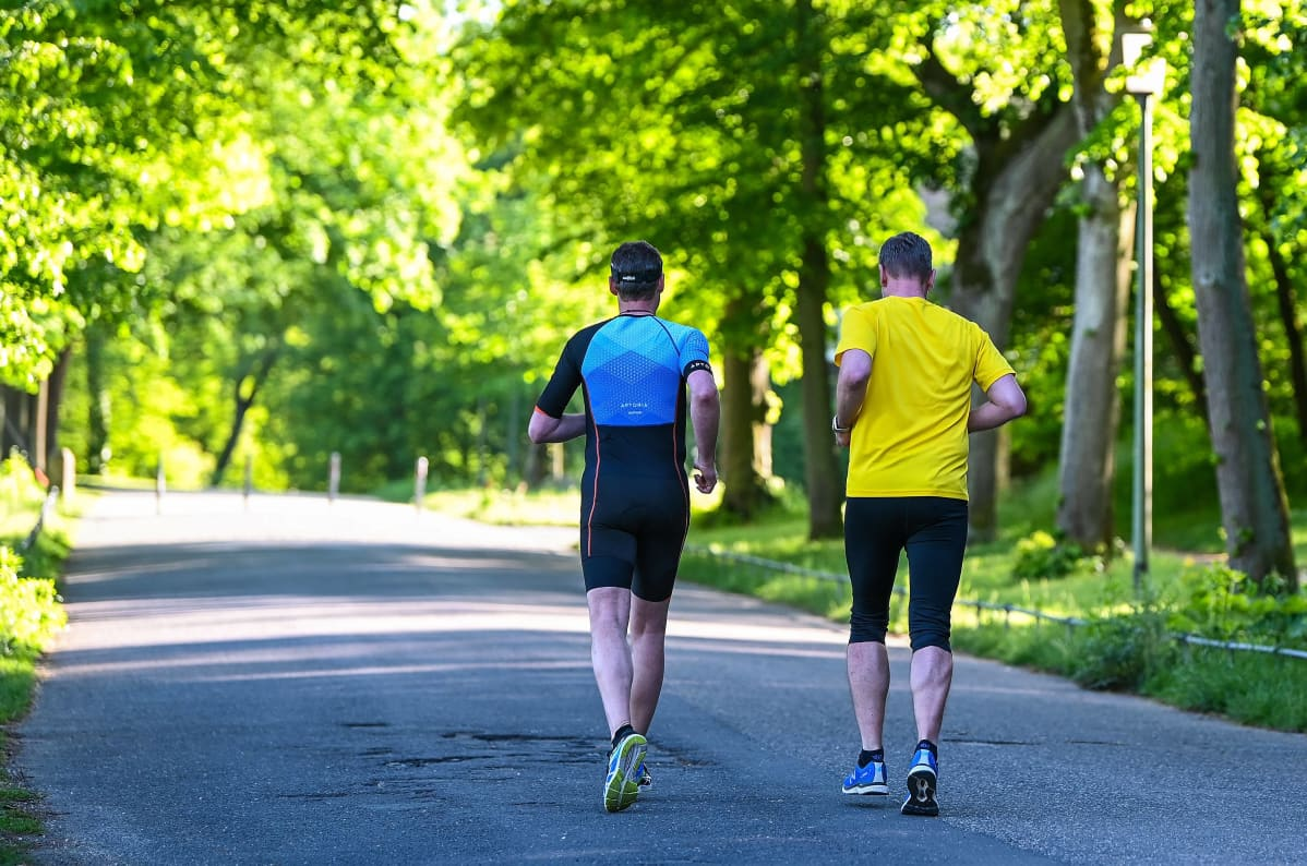 kaksi juoksijaa vehreällä kevyen liikenteen väylällä