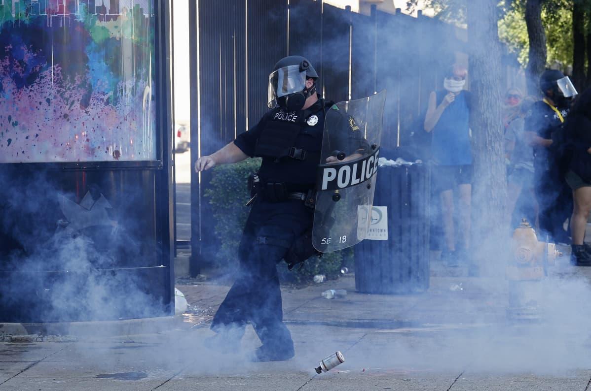 Poliisi potkaisee kyynelkaasupanosta.