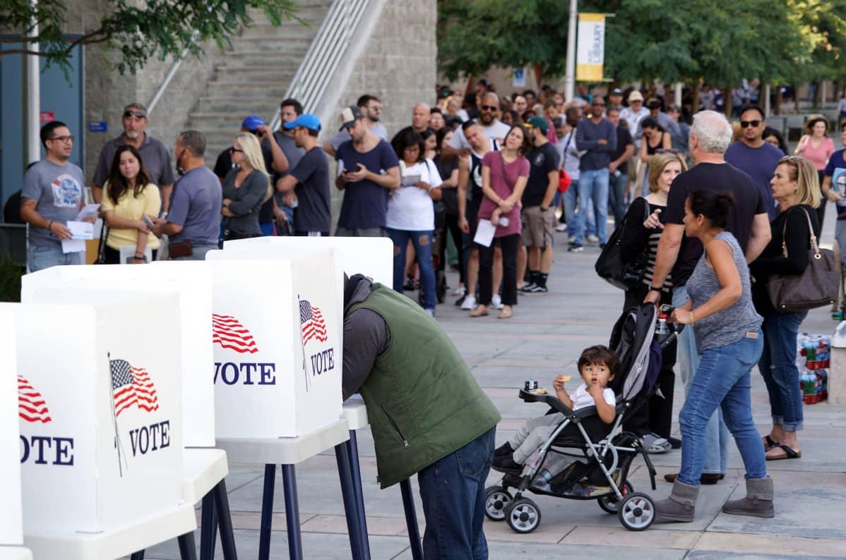 Mies äänestää etualalla pihalla, takana paljon ihmisiä jonottamassa äänestyspaikalle.