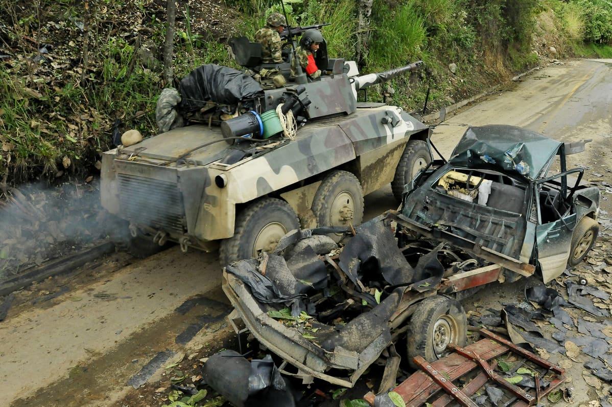 Kolumbian armeijan ajoneuvo ohittaa FARCin pommi-iskussa tuhoutuneen auton jäänteet El Palossa Kolumbiassa helmikuussa 2013.