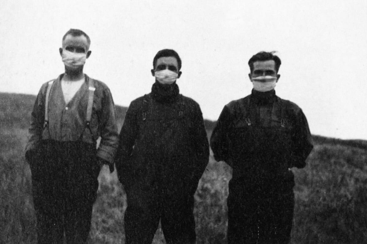 Kolme miestä seisoo rinnakkain, kaikkien kasvoilla on hengityssuojain.