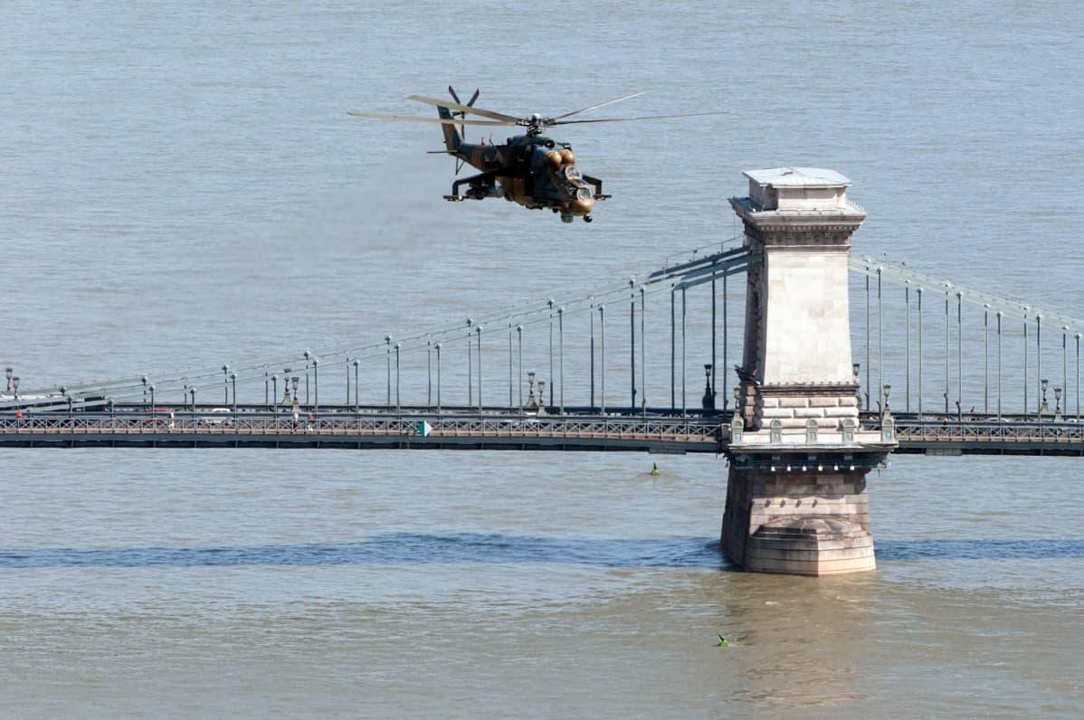 Helikopteri lentää sillan yllä.