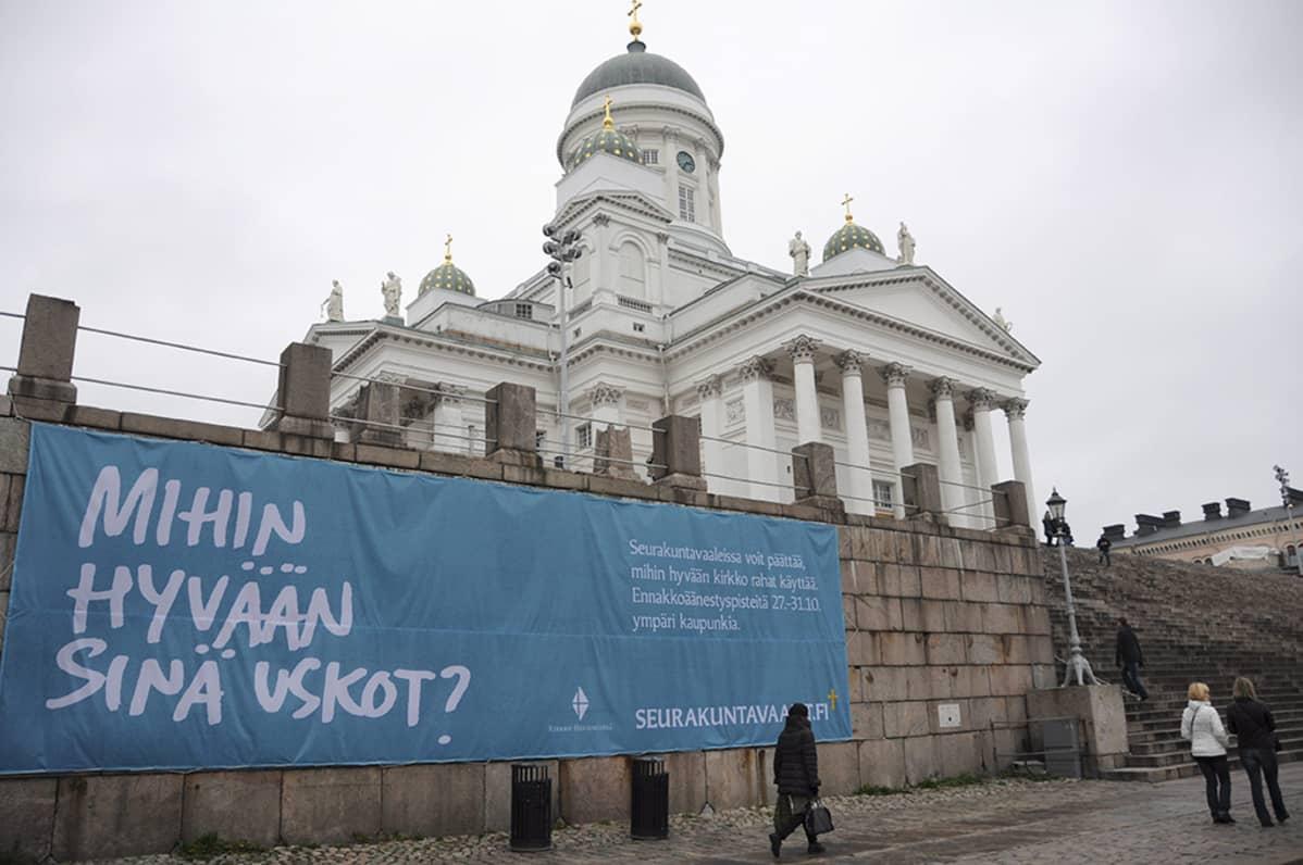 Mihin hyvään sinä uskot? -lause seurakuntavaaleista kertovassa mainoslakanassa Tuomiokirkon edustalla Senaatintorilla Helsingissä 28. lokakuuta 2014.