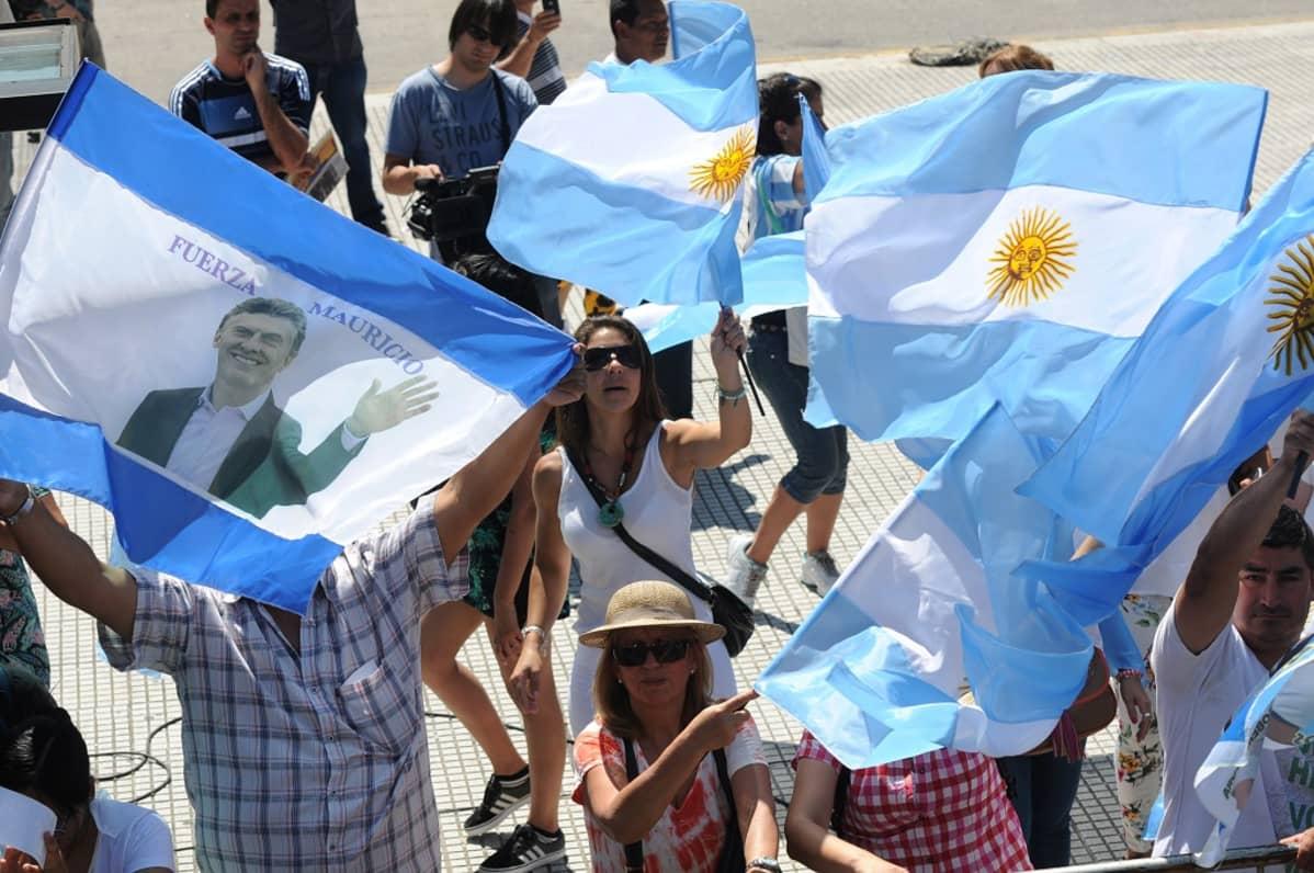 Ihmiset heiluttavat Argentiinan lippuja ja Mauricio Macrin kuvalla varustettua lippua.
