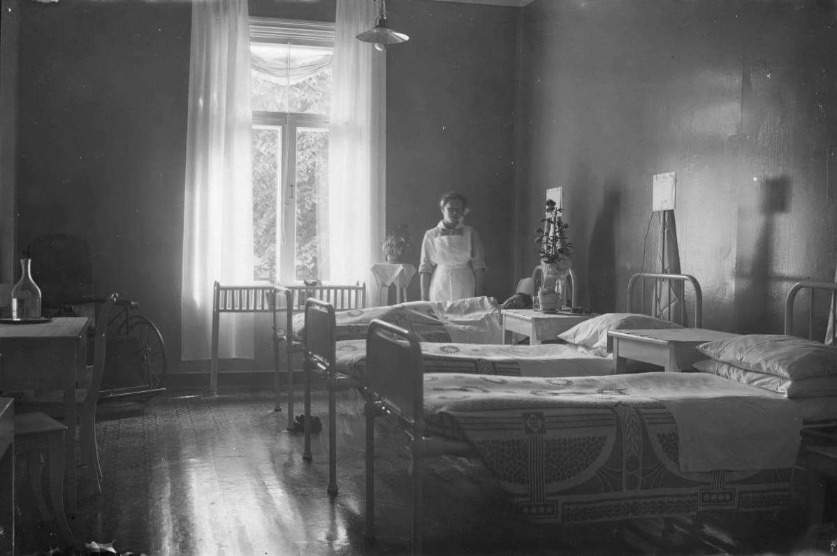 Kuva Finlaysonin sairaalasta. Etualalla kolme pedattua hetekaa, taustalla ikkunan vieressä seisoo sairaanhoitaja essussaan.