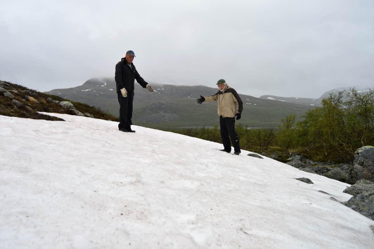 Torstaina otetussa kuvassa kisojen pitkäaikainen latumestari Veikko Aaltonen ja tiedottaja Antti Honkonen seisovat sata metriä pitkän hiihtoalueen keskipisteessä.