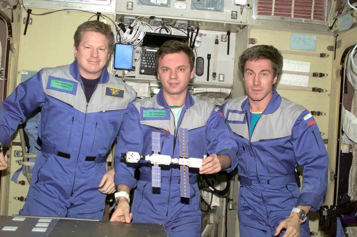 Kolme miestä sinisissä kokohaalareissa, taustalla avaruusaseman laitteistoa.