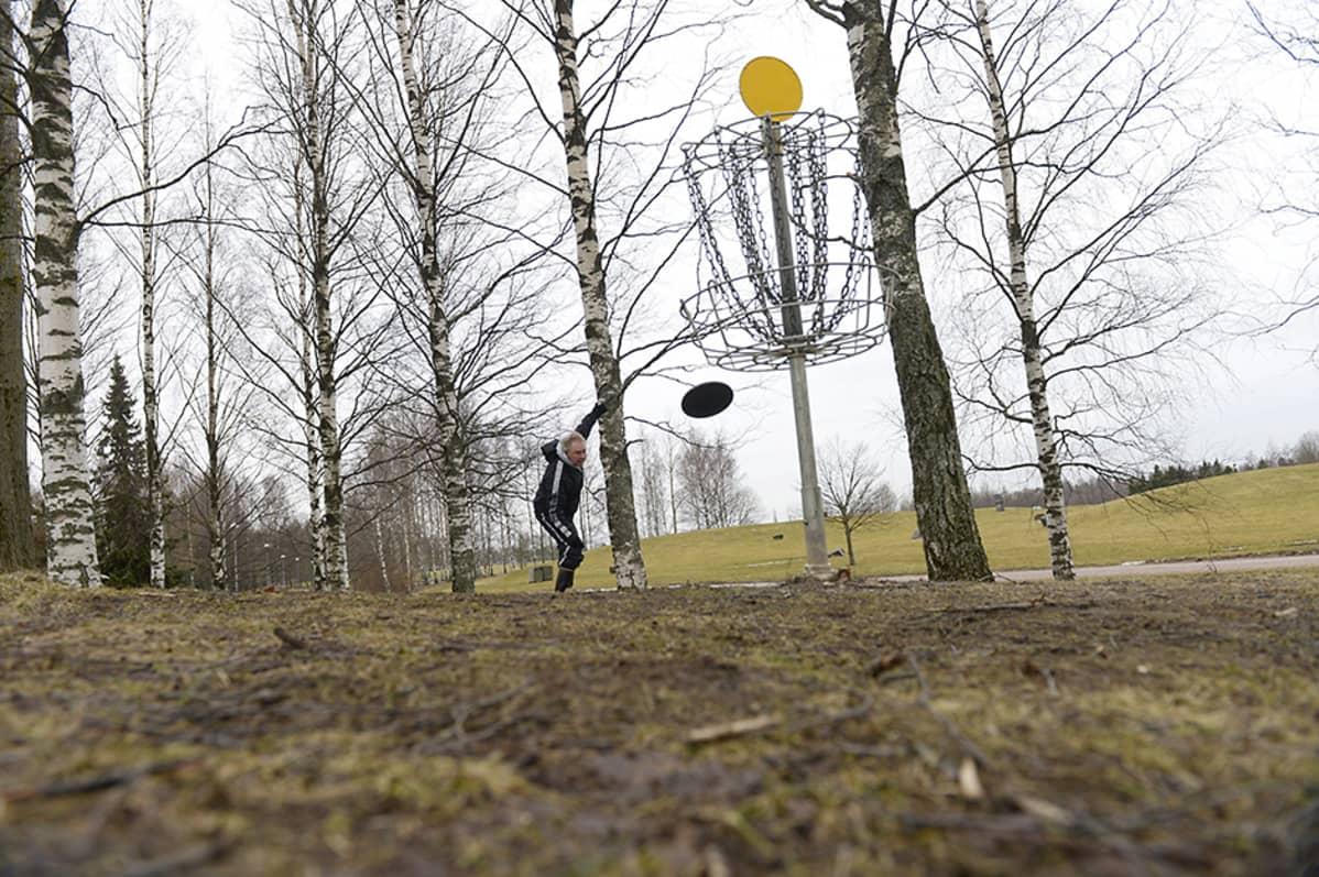 Keski-ikäinen mies frisbee-radalla Siltamäessä Helsingissä 26. helmikuuta 2014. Lunta ei näy missään, maa jopa hieman vihertää.