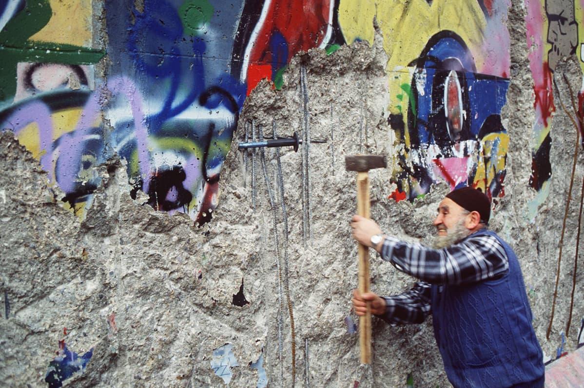 Mies hakkaa Berliinin muuria.