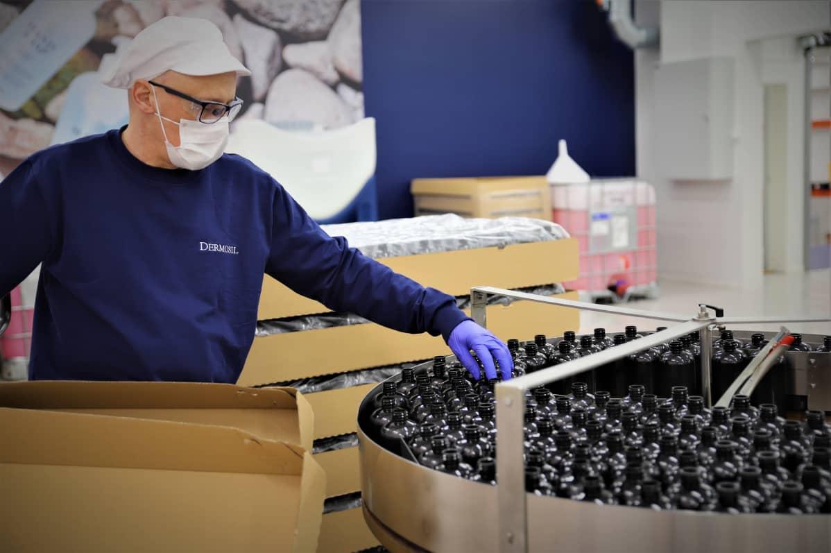 Mies asettaa pulloja laitteeseen