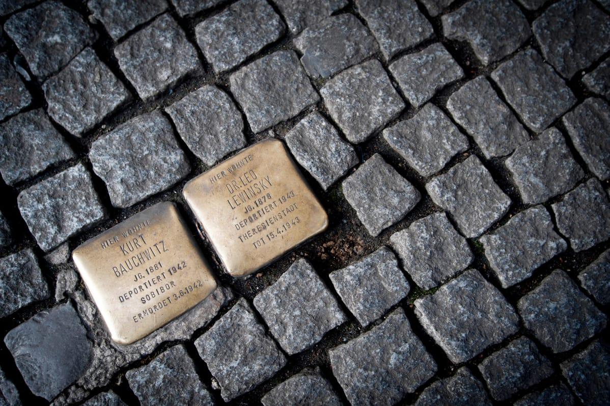 Muistolaattoja kadun kivetyksen seassa.