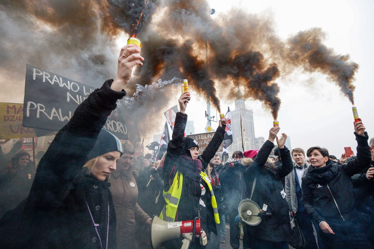ihmiset pitävät savuavia soihtuja kädessään