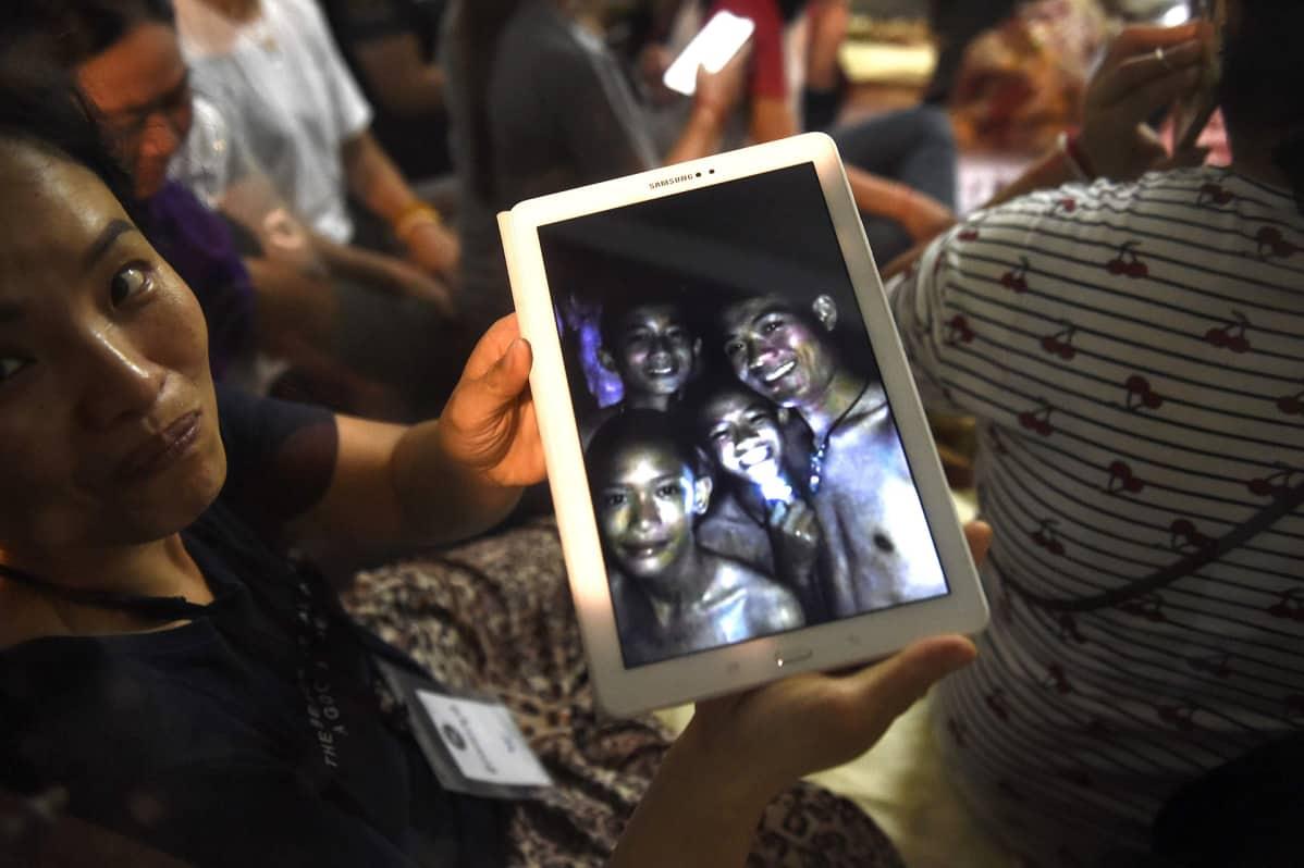 Luolan ulkopuolella odottavat perheenjäsenet katselivat kuvia löytyneitä pojista.