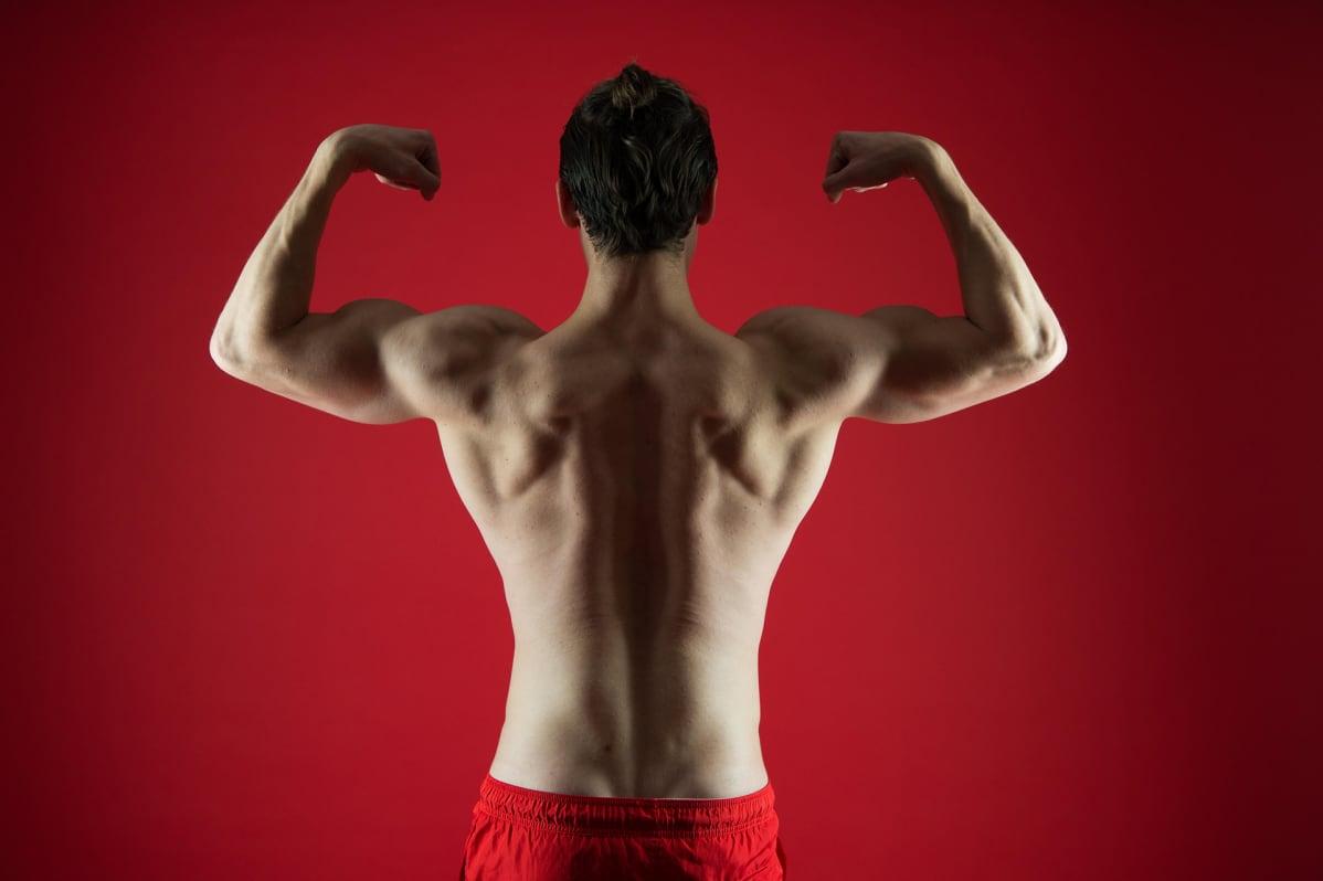mies pullistelee lihaksiaan punaisen seinän edessä