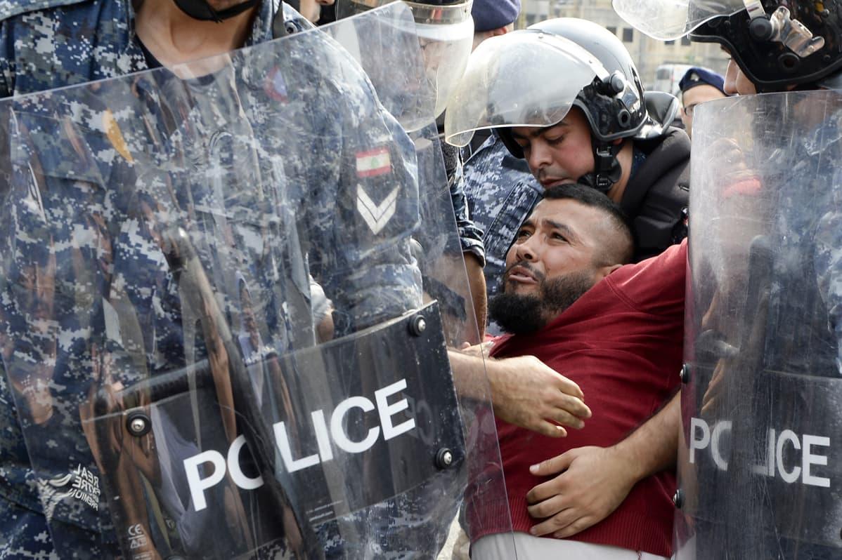 Libanonin mellakkapoliisit poistivat hallituksen vastaisia mielenosoittajia tukkimasta valtatietä Libanonissa Beirutissa 26. lokakuuta. Tuhannet mielenosoittajat jatkoivat veronkorotuksien ja poliitikkojen vastaisia protestejaan toista viikkoa.