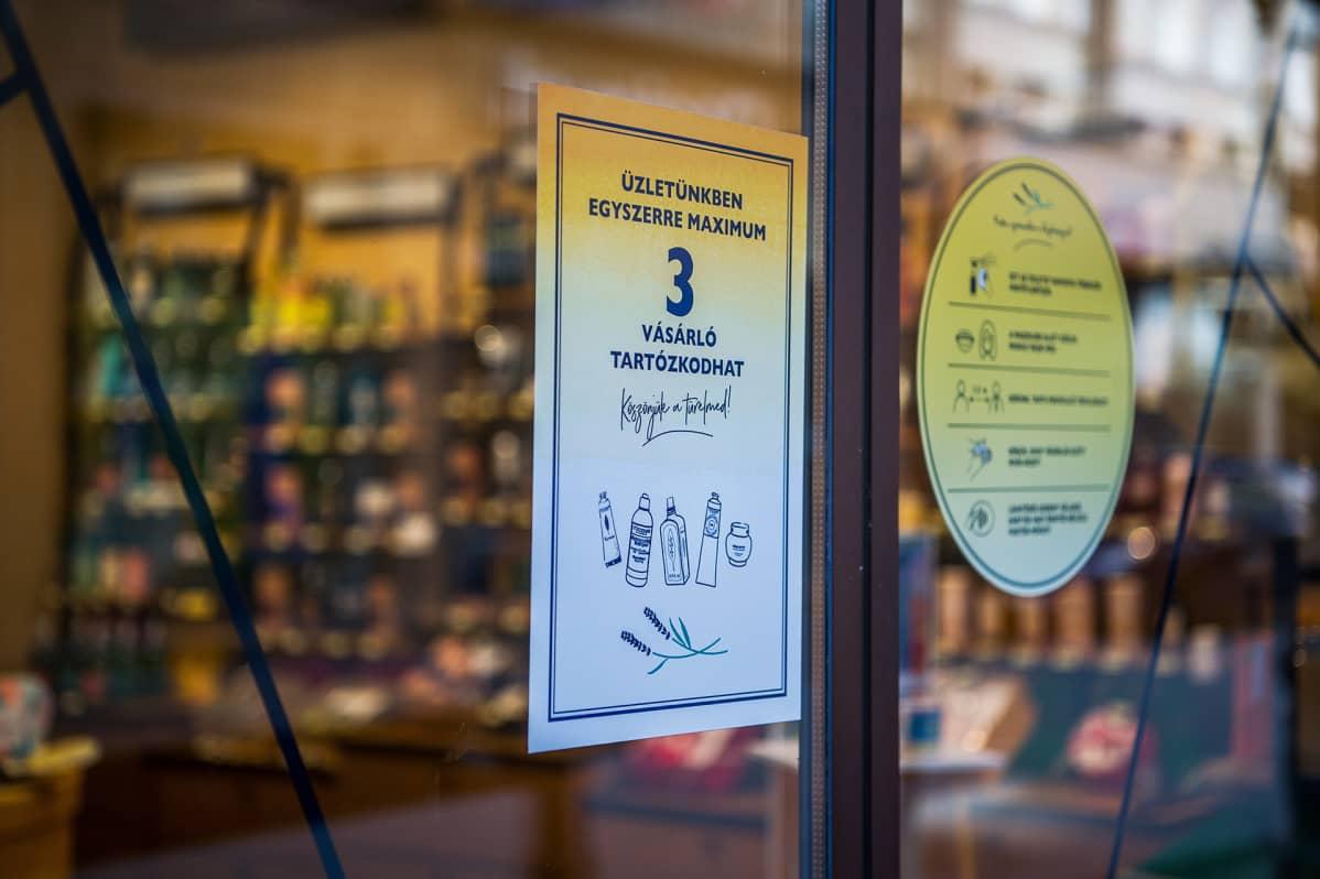 Lappu budapestilaisen kaupan ovessa kertoo, että liikkeessä saa asioida kerrallaan kolme ihmistä.