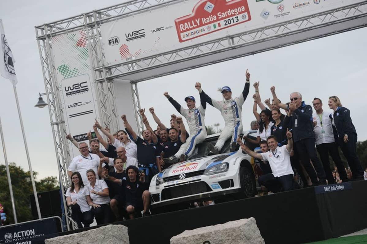 Volkswagenin Julien Ingrassia ja Sebastien Ogier juhlivat Sardinian MM-rallin voittoa yhdessä tallin henkilökunnan kanssa.