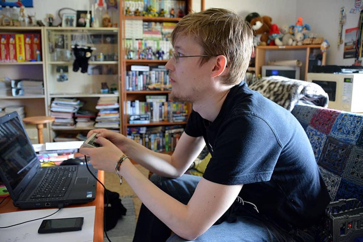 Mies istuu pelaamassa Nintendoa.