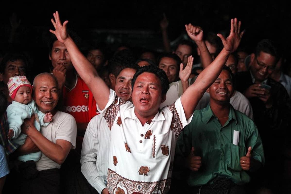 Iloitsevia ihmisiä. Etualalla mies molemmat kädet ylhäällä.