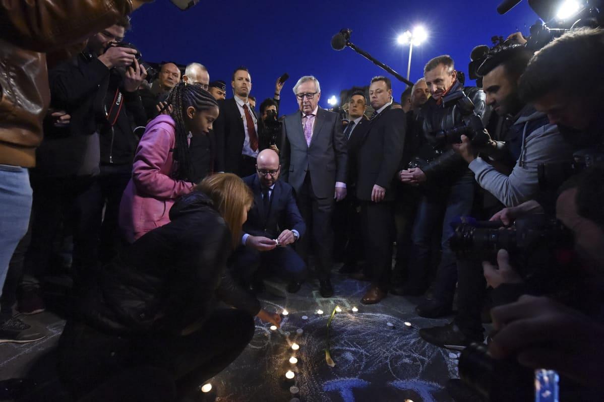 Belgian pääministeri Charles Michel ja Euroopan komission presidentti Jean-Claude Juncker sytyttivät kynttilöitä Bourse -aukiolla kunnioittaakseen terrori-iskujen uhrien muistoa.