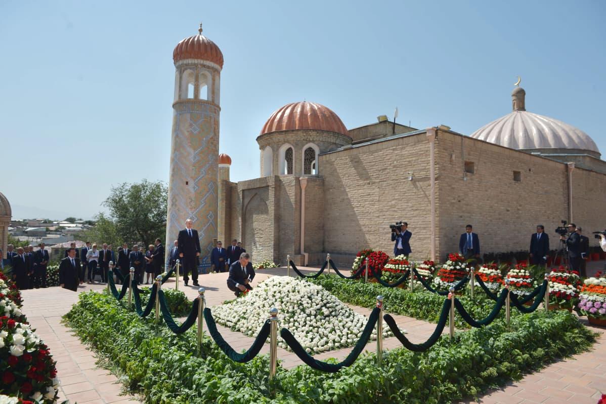 Historiallinen mausoleumi, jonka edessä valkoisin kukin koristelty hauta ja mies polvistuneena haudan takana.
