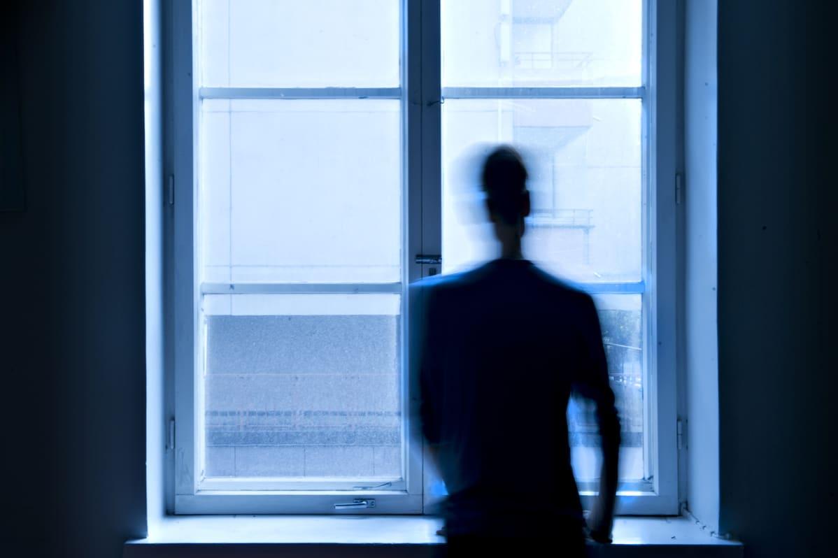 Mies katsoo ikkunasta ulos.
