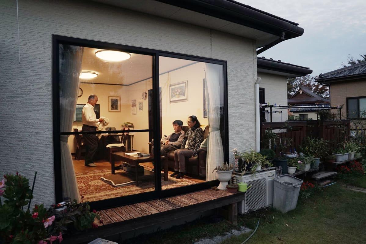 Japanilainen Hayakawan perhe katsoo televisiota. Perhe kuvattuna olohuoneen ikkunan läpi. Äiti ja poika istuvat sohvalla. Isä seisoo sanomalehti kädessään.