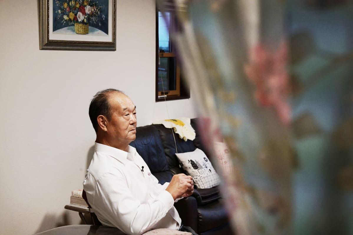Hiroshi Hayakawan istumassa tuolilla olohuoneessaan. Vieressä musta sohva ja seinällä kukkataulu.