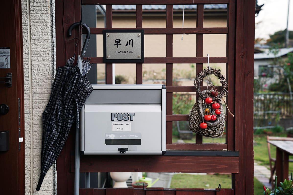 Hayakawan perheen postilaatikko, jonka vieressä roikkuu sateenvarjo ja pieni kori, jossa on punaisia hedelmiä.