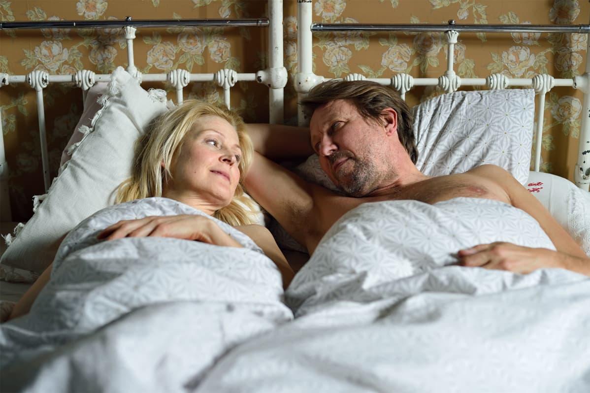 Pariskunta sängyssä.
