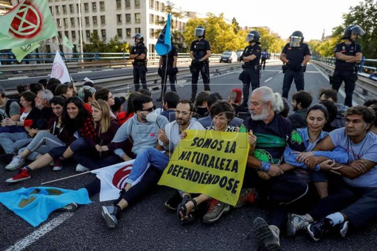 Kuvassa protestoijia istumassa kadulla. Heidän takanaan seisoo poliiseja.