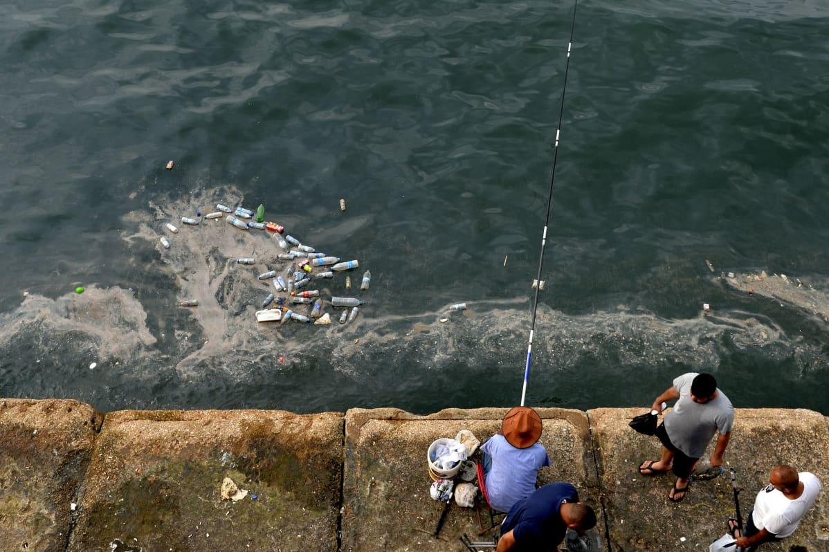 Mies onkii meressä kelluvien muoviroskien lähellä,