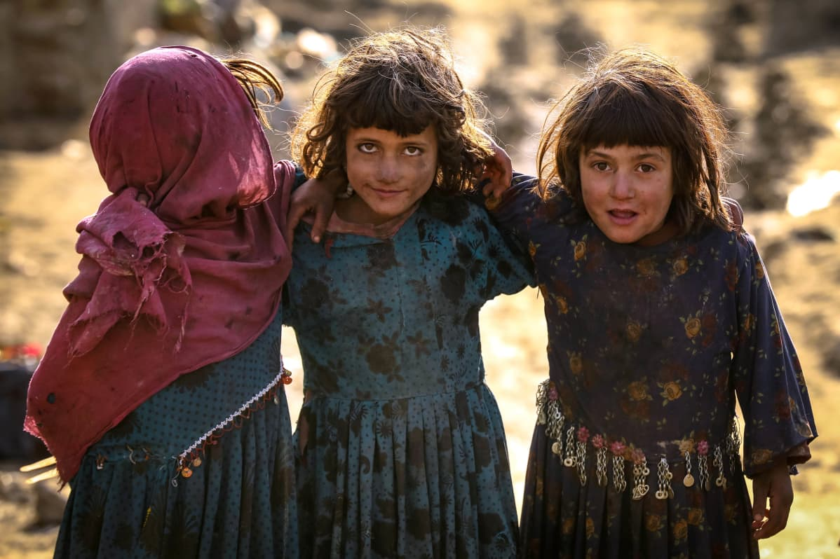 Kolme lasta pitää käsiään toistensa hartioilla.