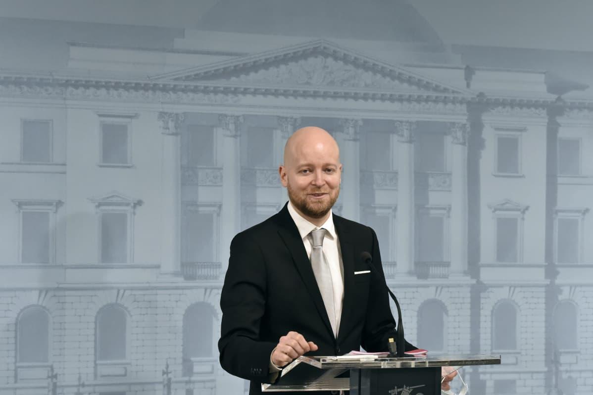 En skallig man står vid ett podium.
