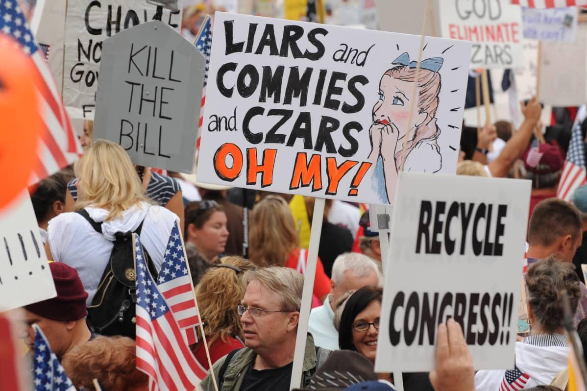 """Mielenosoittajia teekutsuliikkeen tilaisuudessa, kyltissä lukee englanniksi: Liars commies and Czars, Oh my""""."""