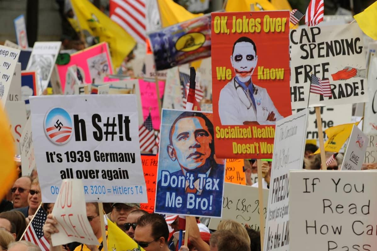 Teekutsuliikkeen mielenosoitusta, kylteissä mm. karikatyyrejä Obamasta.