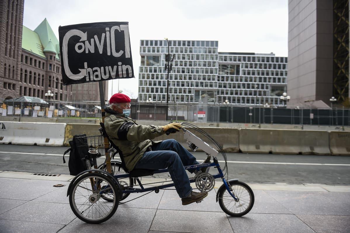 Polkupyöräilevä mielenosoittaja vaati George Floydin kuolemasta syytetyn entisen poliisin tuomitsemista.