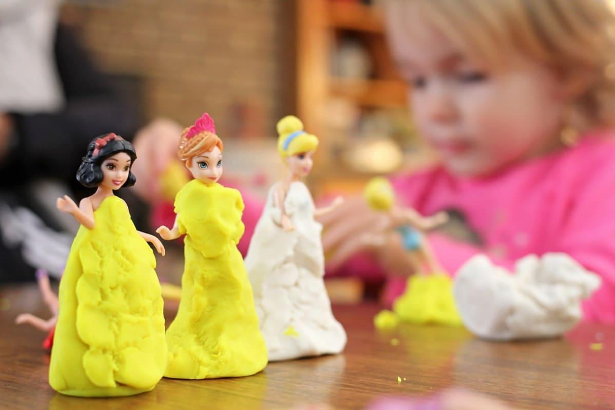 Pikkutyttö pukee  pieniä Disney-nukkeja muovailuvahasta tehtyihin iltapukuihin.