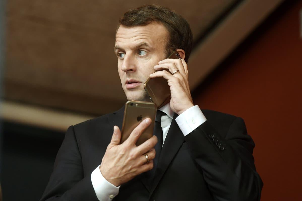 Lähikuva presidentti Emmanuel Macronista kädessään yksi kännykkä, korvalla toinen.