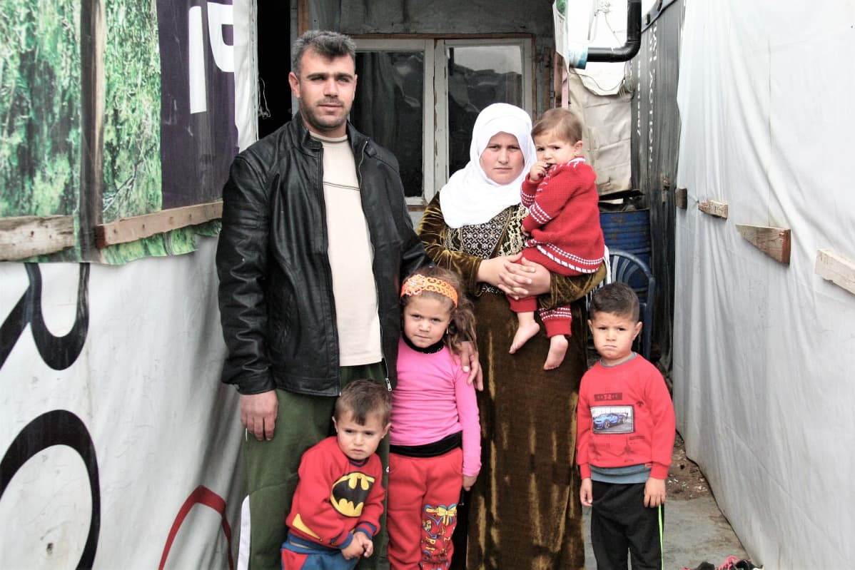 Mies nainen ja lapsia hökkelin edessä