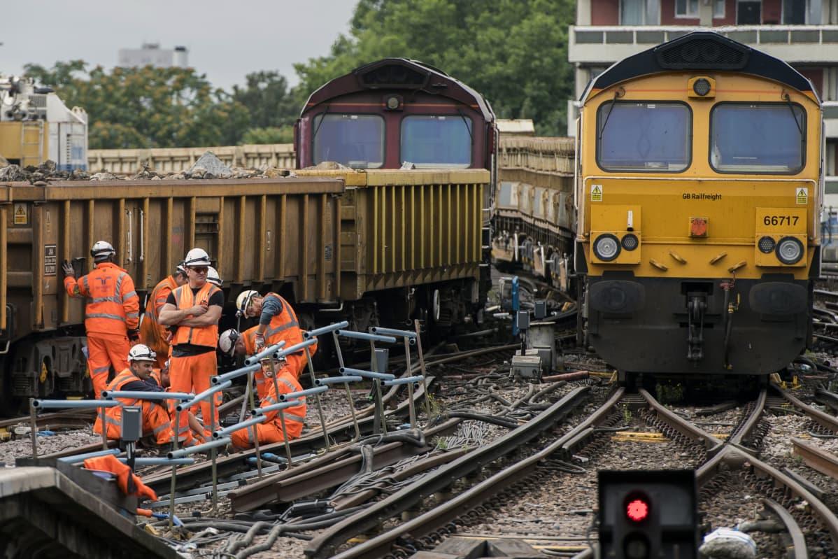 Oransseihin vaatteisiin ja valkoisiin turvakypäröihin pukeutuneita työmiehiä keltaisen junan vieressä.